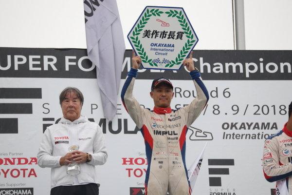 Winner Yuhi Sekiguchi, Itochu Enex Team Impul SF14 Toyota, celebrates on the podium, as team boss Kazuyoshi Hoshino looks on.