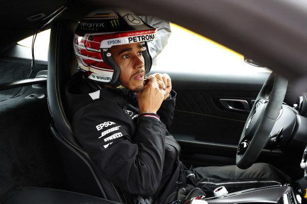 Lewis Hamilton, Mercedes AMG F1, puts on his helmet in the Hot Laps car.