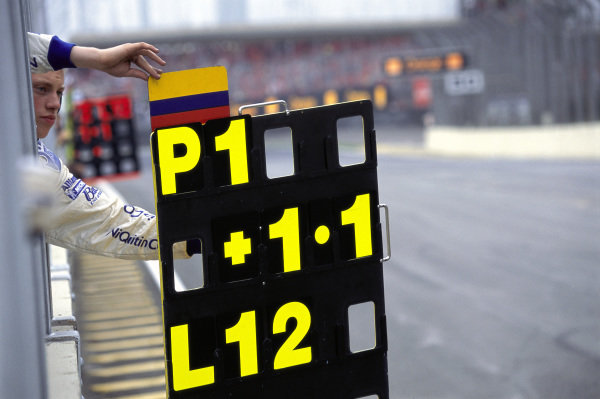 A mechanic holds out the pit board for Juan Pablo Montoya.