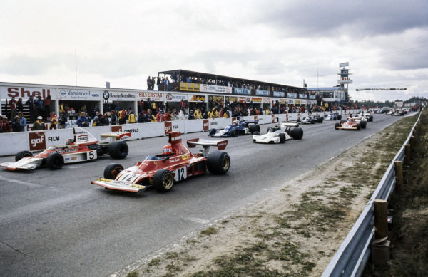 Niki Lauda, Ferrari 312B3 and Emerson Fittipaldi, McLaren M23 Ford line up on the front row of the grid, ready for the start.