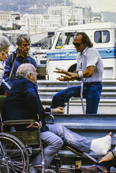 Mike Hailwood on crutches in the pit lane.