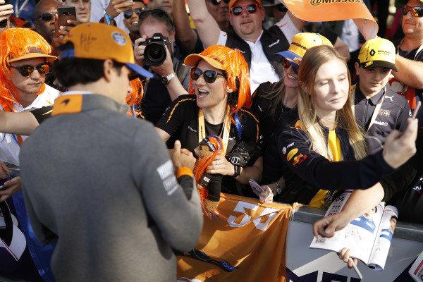 Carlos Sainz Jr, McLaren, signs autographs for fans.