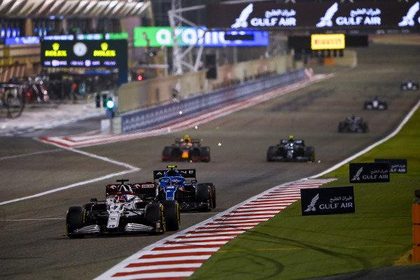 Kimi Raikkonen, Alfa Romeo Racing C41, leads Esteban Ocon, Alpine A521, Sergio Perez, Red Bull Racing RB16B, and Sebastian Vettel, Aston Martin AMR21