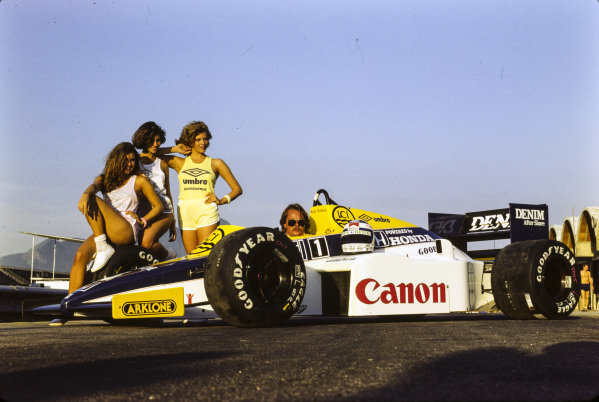 Keke Rosberg, Williams FW10 Honda, sits in cockpit wearing sunglasses. Umbro glamour girls flank the car, while his helmet rests on the sidepod.