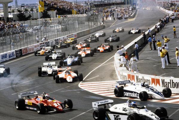 Keke Rosberg, Williams FW08 Ford, leads Riccardo Patrese, Brabham BT50 BMW, Mario Andretti, Ferrari 126C2, John Watson, McLaren MP4-1B Ford, and Derek Warwick, Toleman TG183 Hart, at the start.