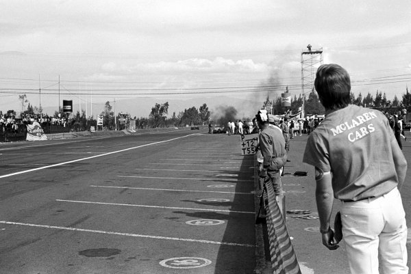 A McLaren employee watches on anxiously as outgoing World Champion Denny Hulme (NZL) McLaren M7A saw his championship hopes end when a suspension failure crashed him out of the race on the pit straight.  Mexican Grand Prix, Mexico City, 3 November 1968.