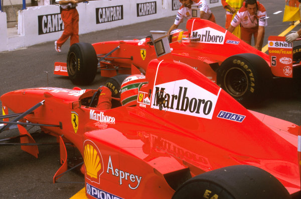 Monza, Italy.5-7 September 1997.Eddie Irvine (Ferrari F310B) goes out as Michael Schumacher comes in.Ref-97 ITA 15.World Copyright - LAT Photographic