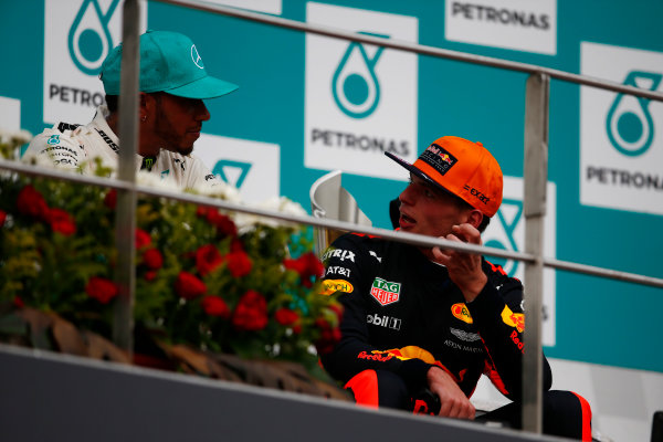Sepang International Circuit, Sepang, Malaysia. Sunday 1 October 2017. Lewis Hamilton, Mercedes AMG, 2nd Position, and Max Verstappen, Red Bull, 1st Position, talk on the podium. World Copyright: Andrew Hone/LAT Images  ref: Digital Image _ONY5412
