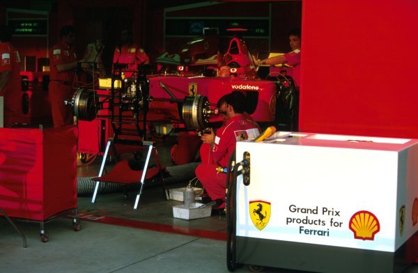 Ferrari mechanics work on a dominant F2002 in the pit garage.