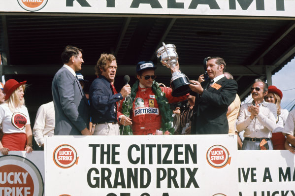 Kyalami, South Africa. 4-6 March 1976. Niki Lauda, Ferrari, receives the winner's trophy on the podium. Ref: 76SA11. World Copyright - LAT Photographic