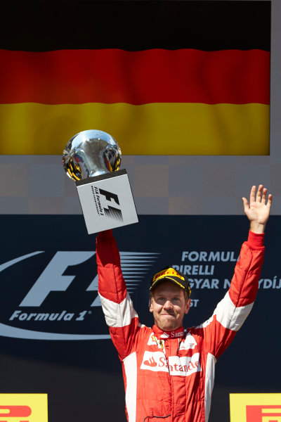 Hungaroring, Budapest, Hungary. Sunday 26 July 2015. Sebastian Vettel, Ferrari, 1st Position, with his trophy on the podium. World Copyright: Steve Etherington/LAT Photographic ref: Digital Image SNE14313