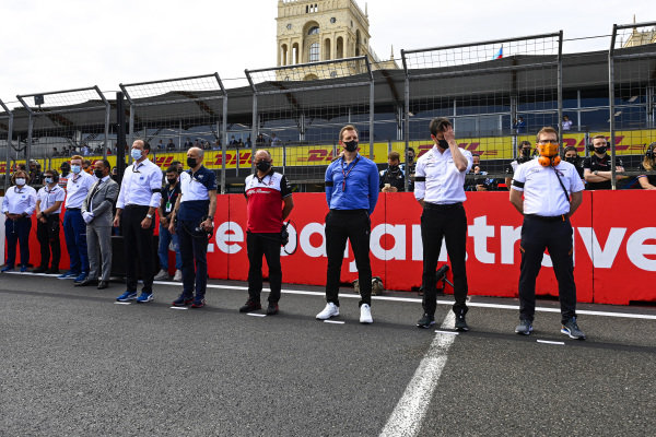 Team members stand for a minutes silence for the late Mansour Ojjeh prior to the start