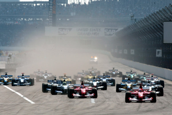 2002 American Grand Prix.Indianapolis, Indiana, USA. 27-29 September 2002.Michael Schumacher and Rubens Barrichello (both Ferrari F2002's) lead the field at the start.World Copyright - LAT Photographicref: Digital File Only