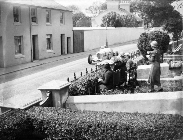 Fans watch from their front garden as Vasco Sameiro, Alfa Romeo Monza, passes.